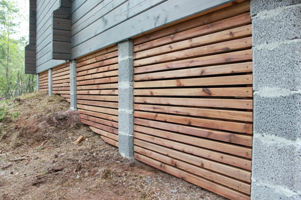 Painekyllästetystä puusta tehdyt suojaritilät toimivat näkösuojana ja viimeistelevät hirsirakennuksen ulkonäön.
